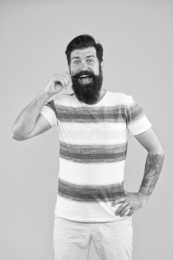 Feeling playful. bearded man hipster yellow wall. mature brutal guy striped shirt. male fashion barbershop. summer royalty free stock photos