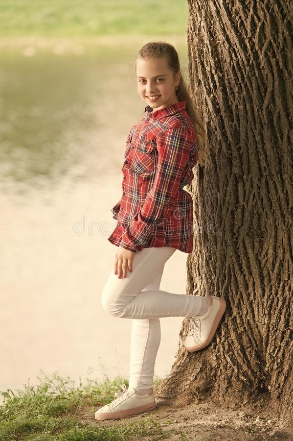 Feeling relaxed. Adorable girl with long blond hair in casual plaid style. Little girl wearing fashion summer outfit. Small girl child with beauty look royalty free stock image