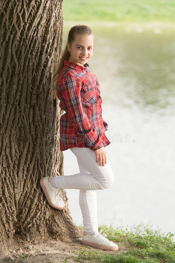 Feeling relaxed. Adorable girl with long blond hair in casual plaid style. Little girl wearing fashion summer outfit. Small girl child with beauty look royalty free stock photos