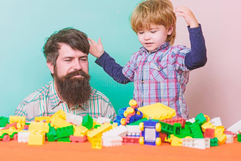 Feeling safe with dad. small boy with dad playing together. father and son play game. building home with colorful royalty free stock photos