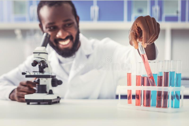 Professional chemist feeling satisfied after making research. Feeling satisfied. Professional skillful chemist feeling extremely satisfied after making prominent royalty free stock image