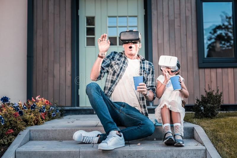Emotional father and daughter feeling scared wearing virtual reality glasses royalty free stock photos