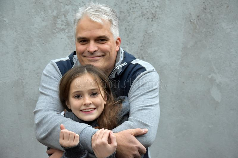 Feeling of security. Father cuddles his sweet teenage daughter and gives her a feeling of security stock image