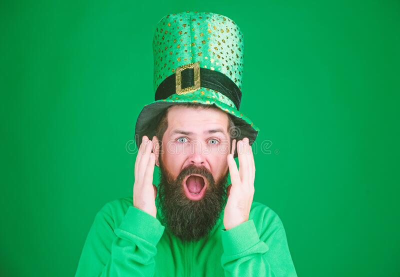 Feeling shocked. Bearded man keeping mouth open while celebrating saint patricks day. Hipster in leprechaun hat and royalty free stock photos