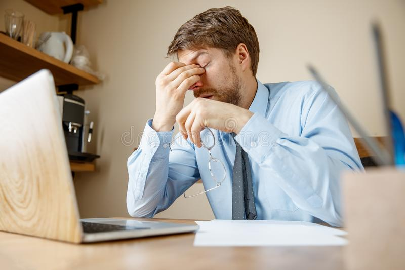 Feeling sick and tired. Frustrated young man massaging his head while sitting at his working place in office. Feeling sick and tired. Frustrated sad unhappy sick stock photos