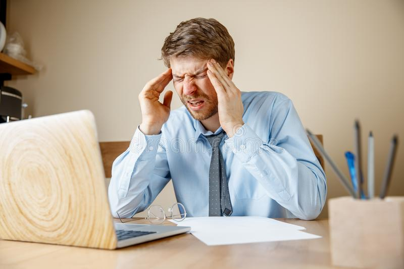Feeling sick and tired. Frustrated young man massaging his head while sitting at his working place in office. Feeling sick and tired. Frustrated sad unhappy sick stock images