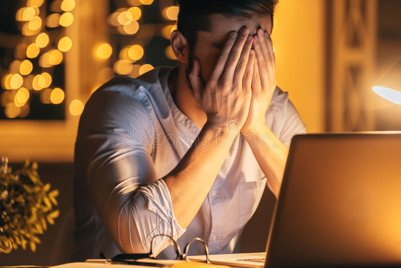 Feeling sick and tired. Frustrated young man covering face with hands while sitting at his working place at night time with Christmas lights in the background stock photography