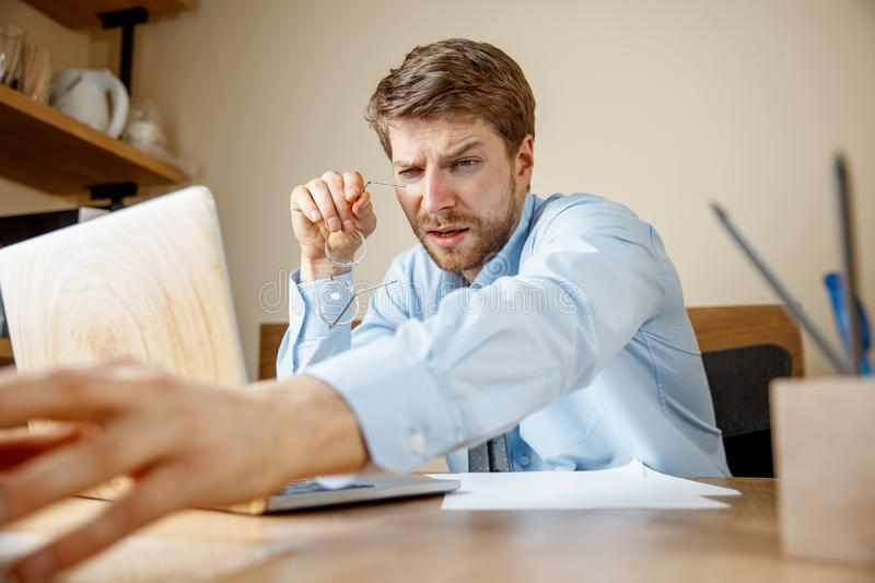 Feeling sick and tired. Frustrated young man massaging his head while sitting at his working place in office. Feeling sick and tired. Frustrated sad unhappy sick stock photography