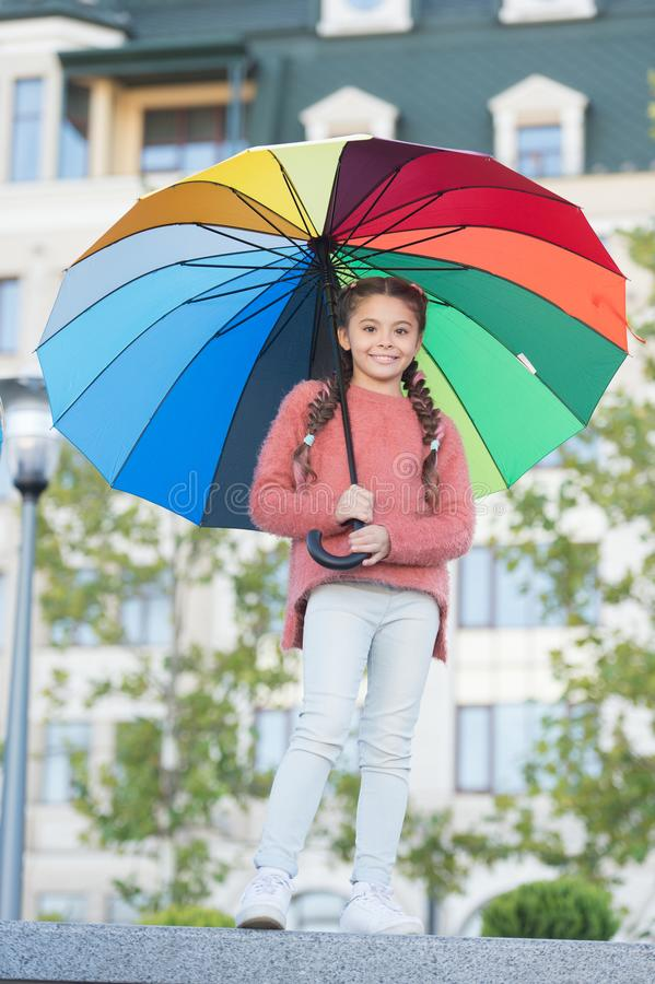 Feeling warm. Optimist and cheerful child. Spring warm. Positive mood in autumn warm weather. Multicolored umbrella for stock photography