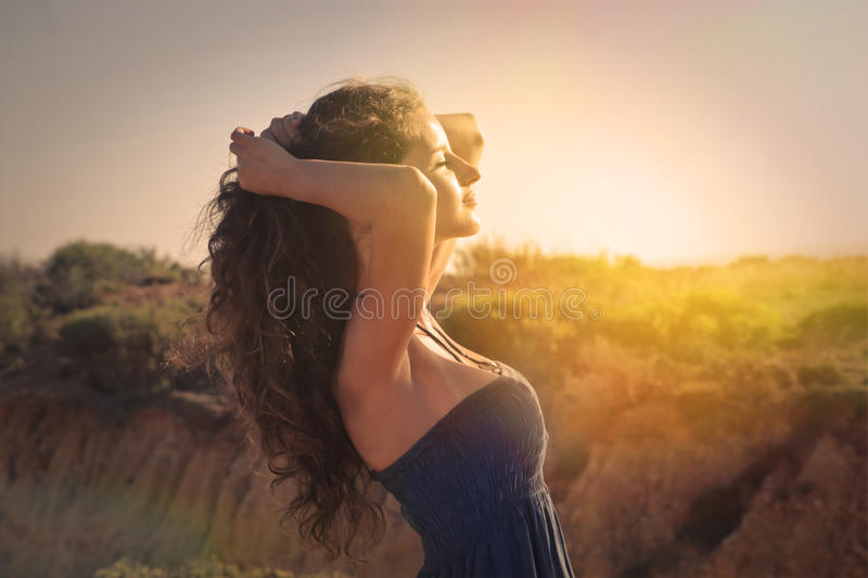 Feeling the warmth. A girl is feeling the warmth of the sun on her skin stock image