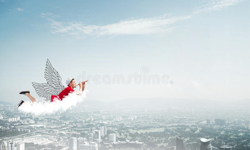 Feeling young and free. Young cheerful man flying high above city and playing fife royalty free stock photography