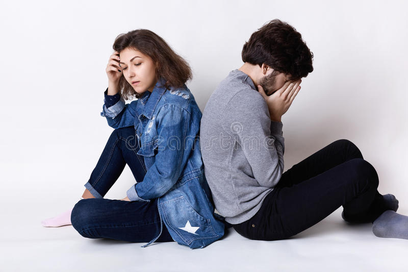 Feelings and attitudes. A couple sitting on the floor backs having tired and sad expression after a little quarrel. Couple having stock photo