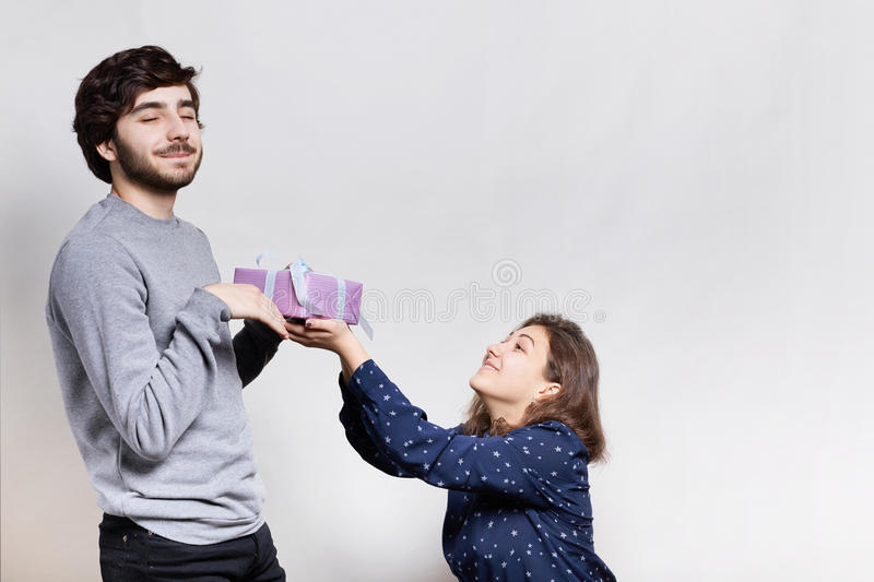 Feelings and relationships concept. A smiling young woman giving a present to her boyfriend. A pleased bearded hipster with closed royalty free stock photo