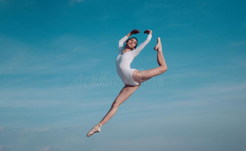 Feels like flying. Young ballerina jumping on blue sky. Pretty girl in dance wear. Cute ballet dancer. Concert stock photo