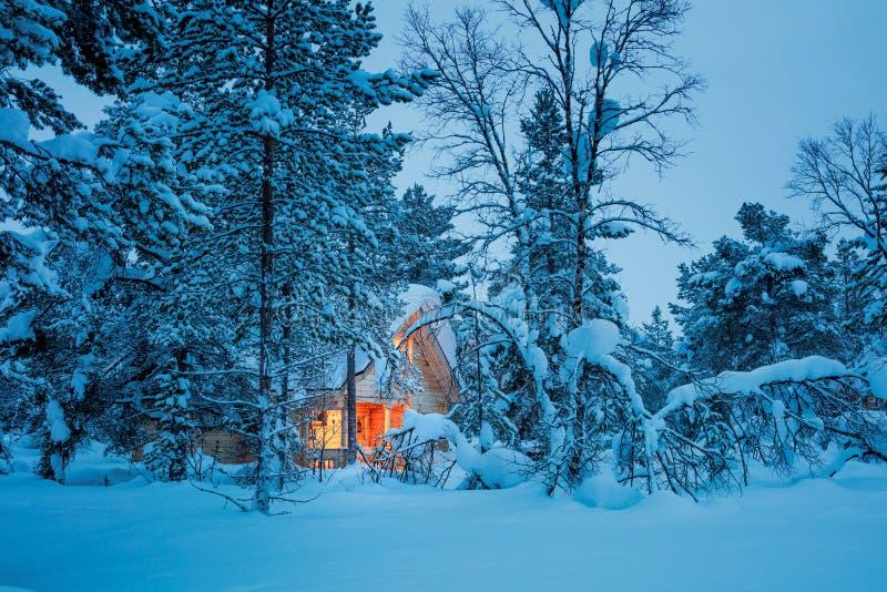 Feenhafte Nacht des Winters - Holzhaus im blauen schneebedeckten Wald lizenzfreie stockbilder