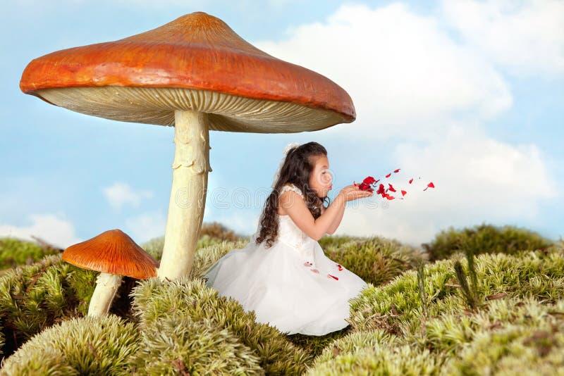 Feenhaftes Mädchen, das rosafarbene Blumenblätter durchbrennt stockbild
