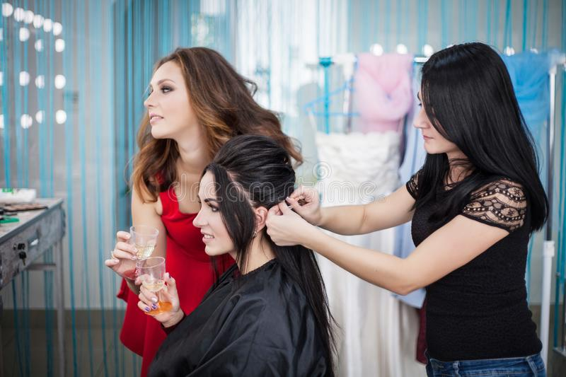 Fees bride. Hen-party. Young woman doing hairstyle at the hairdresser in the beauty salon stock photo