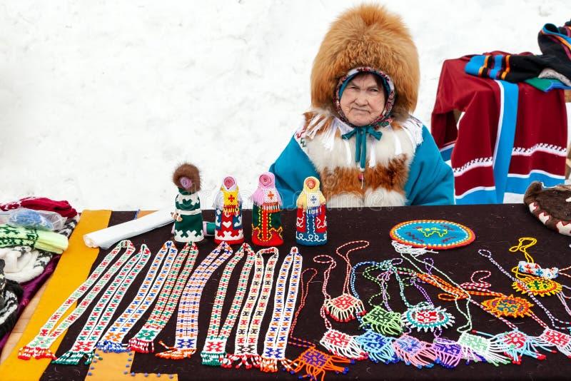 Feest van rendierherders en fishermans Een vrouw in nationaal kostuum verkoopt traditionele herinneringen van het Noorden stock afbeeldingen