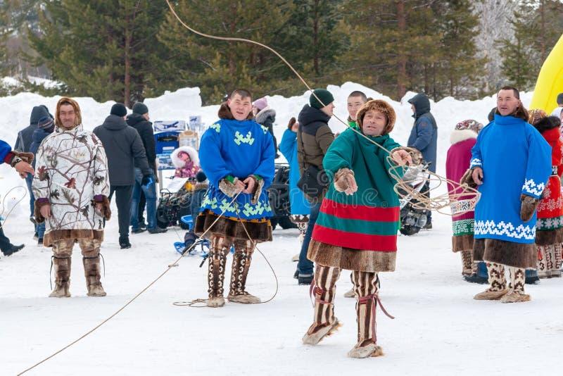 Feest van rendierherders en fishermans Rendierherders in nationale kostuums nemen aan lasso deel werpend competities stock afbeelding