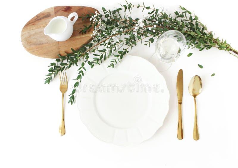 Feestelijk huwelijk, verjaardagslijst met gouden bestek plaatsen, eucalyptusparvifolia, glas wijn en melkwaterkruik die royalty-vrije stock afbeelding