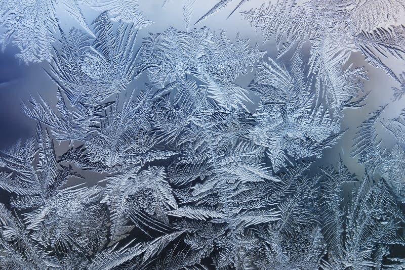 feestelijk ijzig patroon met witte sneeuwvlokken op een blauwe achtergrond op glas stock afbeelding