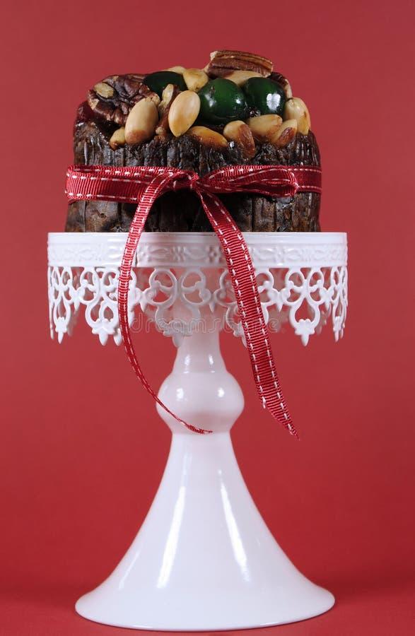 Feestelijk Kerstmisvoedsel, fruitcake met glacekersen en noten op witte cake tegen een rode achtergrond royalty-vrije stock afbeeldingen
