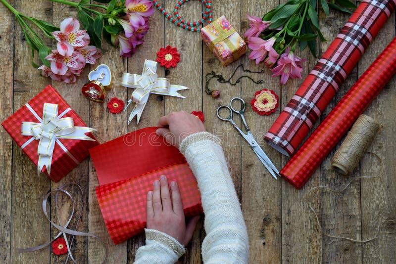 Feestelijke achtergrond De hoogste meningssamenstelling van vrouwenhanden verpakt heden voor Verjaardag, Moedersdag, Valentijnska royalty-vrije stock foto's