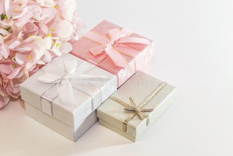 Feestelijke achtergrond met giftomslag met roze, zilveren, grijze dozen met boog en bloemen van kunstmatige hydrangea hortensia i royalty-vrije stock afbeeldingen