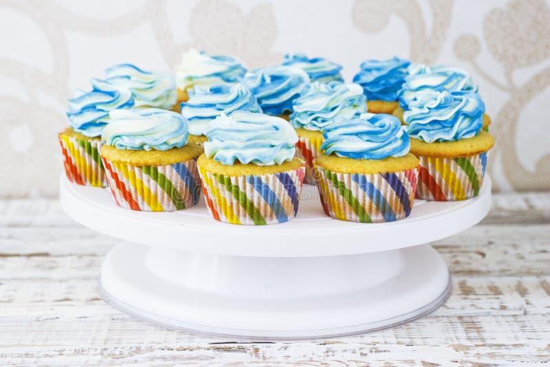 Feestelijke cupcakes met room in blauw op een witte houten achtergrond stock afbeelding
