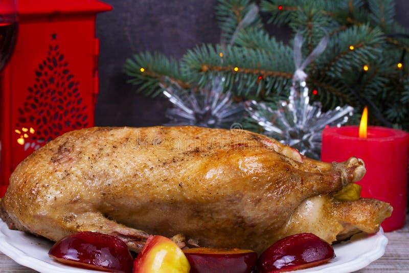Feestelijke die Kerstmiseend met appelen en pruimen wordt gebakken: glazen wijn stock foto