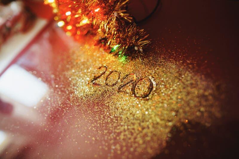 Feestelijke figuur 2020, die op een Bordeauxachtergrond wordt geschreven met fonkelingen Nieuw jaar`s concept royalty-vrije stock foto's