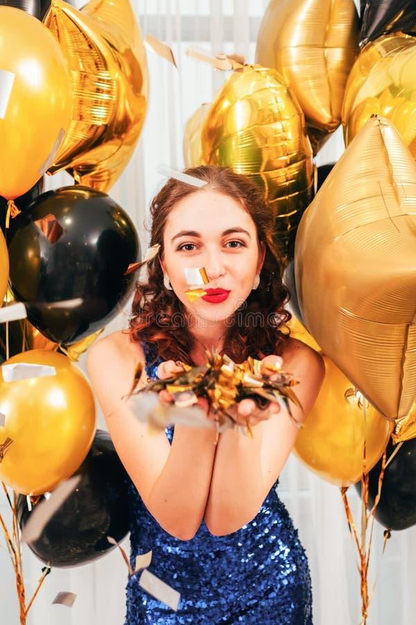 Feestelijke het meisjes blazende confettien van gelegenheidsballons stock afbeelding