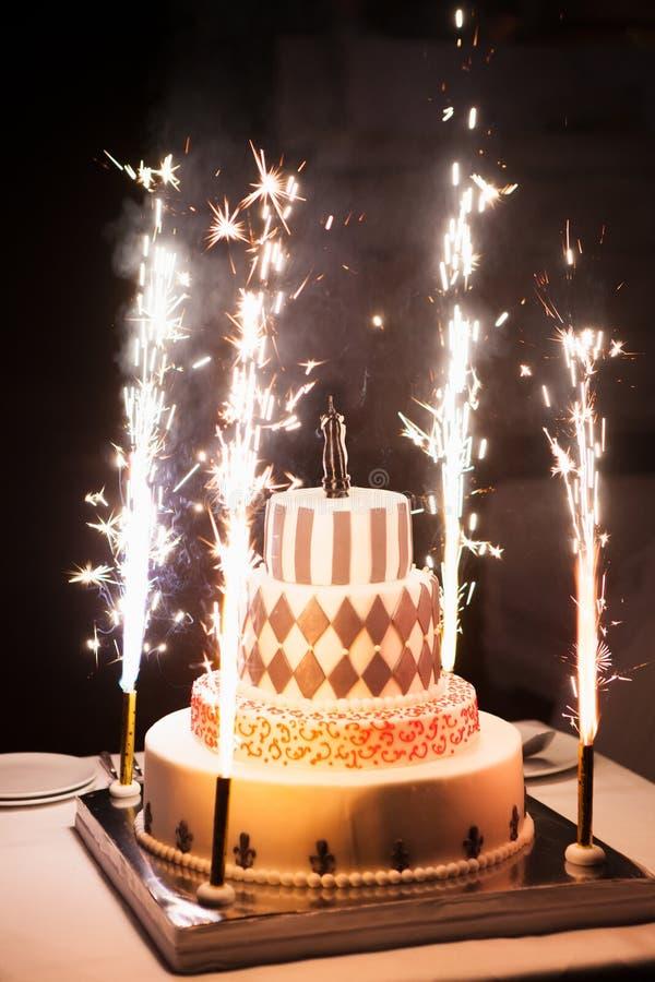 Feestelijke huwelijkscake met vuurwerk op een donkere achtergrond stock afbeelding