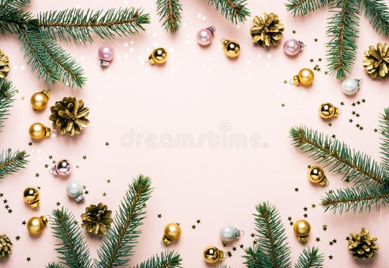 Feestelijke kader van pastelkleur vertakt het Roze Kerstmis zich van spar, gouden ballen en confettien stock foto