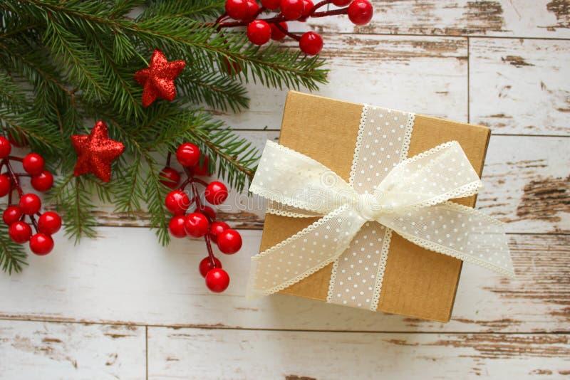 Feestelijke Kerstmisachtergrond De giftdoos met witte boogspar vertakt zich met rode bessen en sterren op witte houten achtergron stock afbeeldingen