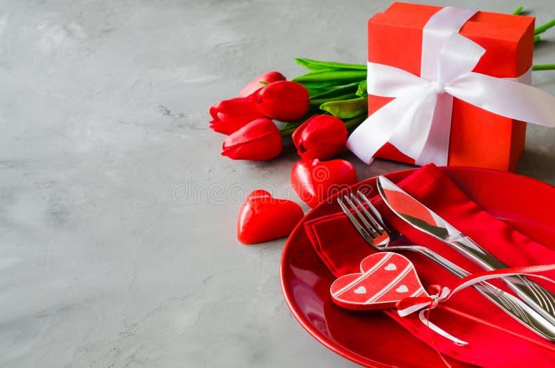 Feestelijke lijst die voor de Dag van Valentine met giftvakje en tulpen plaatsen royalty-vrije stock fotografie