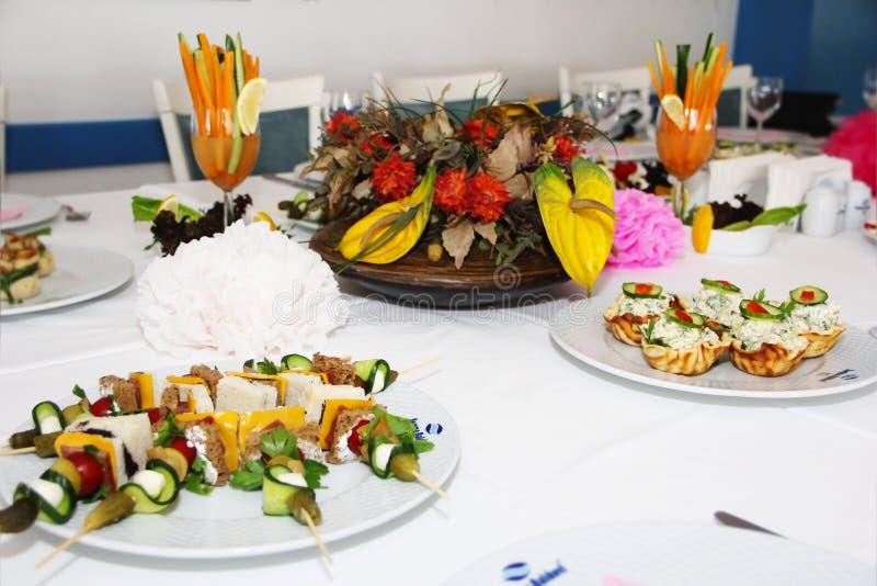 feestelijke lijstdecoratie met salades, snacks en een boeket van bloemen stock foto