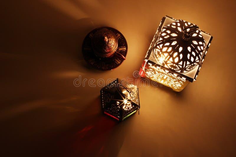 Feestelijke lijstsamenstelling van de gloeiende Marokkaanse sierlantaarns en kop van de bronsthee Decoratieve gouden schaduwen royalty-vrije stock afbeeldingen