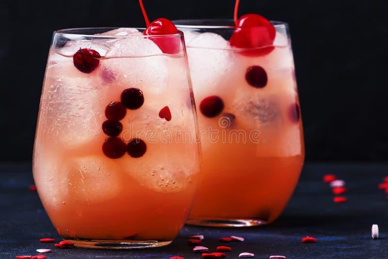 Feestelijke roze koude alcoholische cocktail met rode marasquinkersen voor Valentijnskaartendag, twee glazen, zwarte achtergrond  royalty-vrije stock afbeeldingen