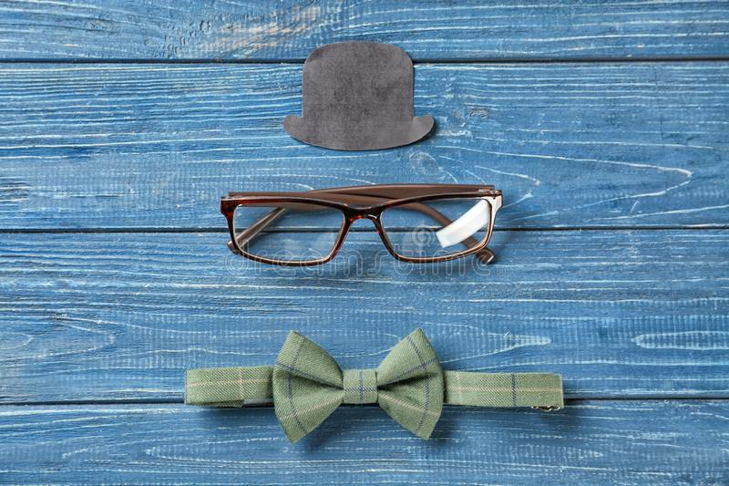 Feestelijke samenstelling met oogglazen, document hoed en vlinderdas op houten achtergrond Gelukkige Vader\ 's Dag stock foto