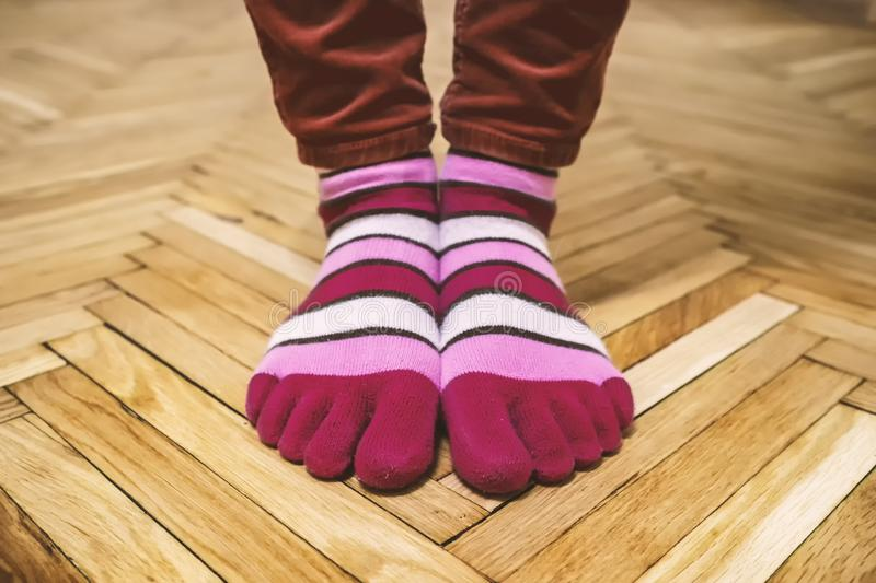 Feet in amusing multi-colored striped socks stand on an old parquet royalty free stock photo