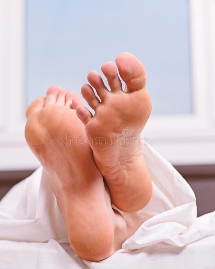 Feet appear out of blanket close up. Man sleeping on bed under blanket. Sleep alone. Healthy skin on foot. Size of foot. Male feet on bed in morning. Fresh and royalty free stock image