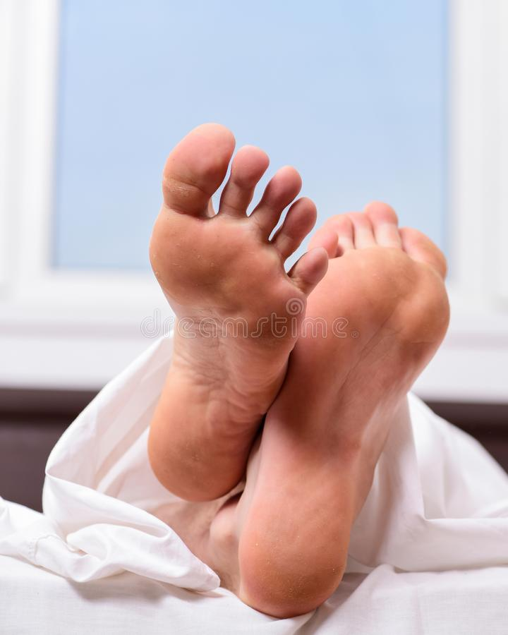 Feet appear out of blanket close up. Man sleeping on bed under blanket. Sleep alone. Healthy skin on foot. Size of foot. Male feet on bed in morning. Fresh and royalty free stock photography