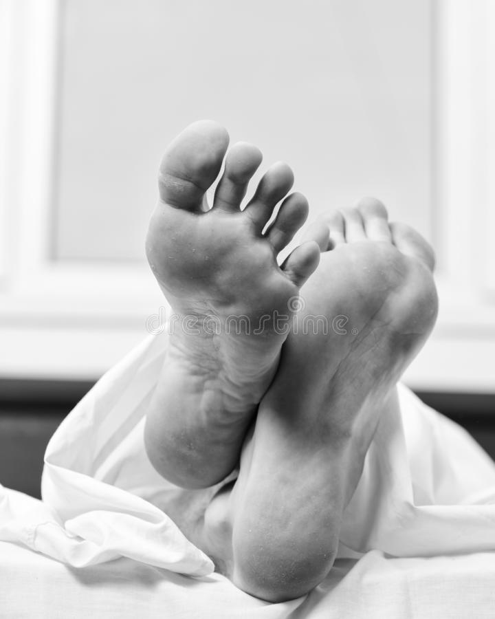Feet appear out of blanket close up. Man sleeping on bed under blanket. Sleep alone. Healthy skin on foot. Size of foot. Male feet on bed in morning. Fresh and royalty free stock photos