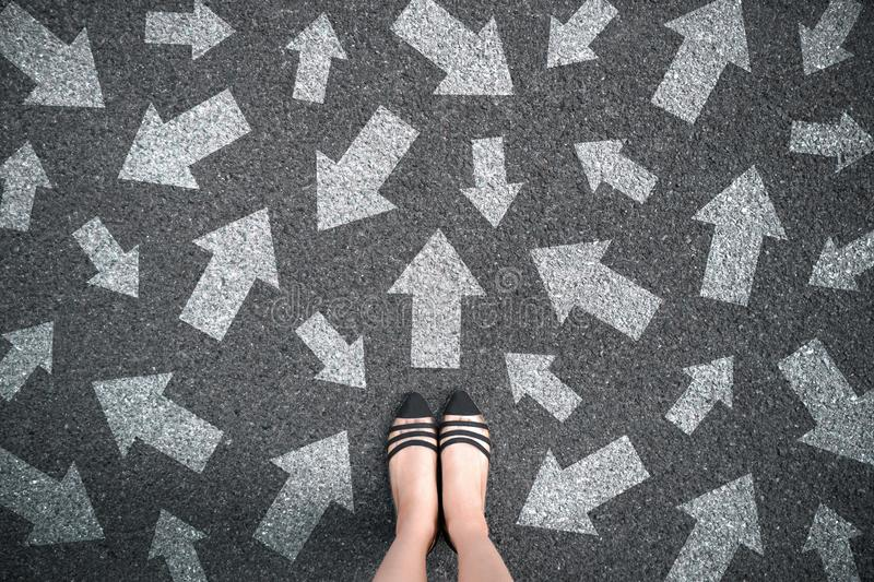 Feet and arrows on road background. Woman standing with many direction sign arrow choices in different ways, left and forward. stock images