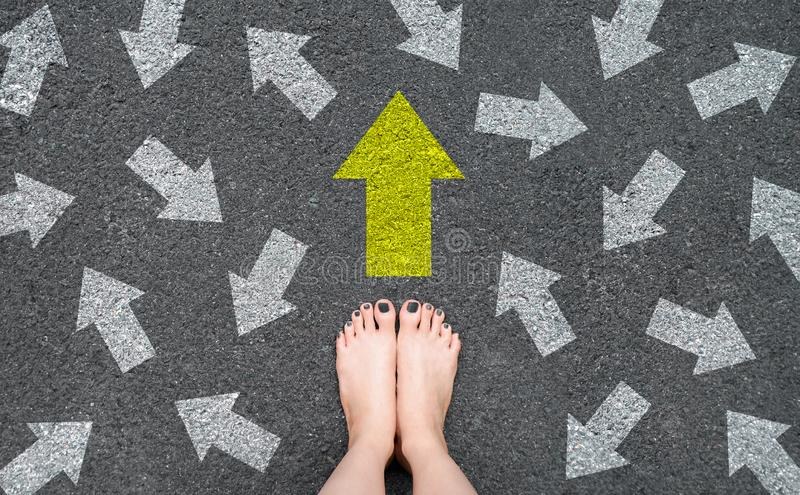 Feet and Arrows on Road. Woman Bare Feet with Gray Nail Polish Manicure Standing on Grunge Concrete with Many White Arrow Sign and stock photos