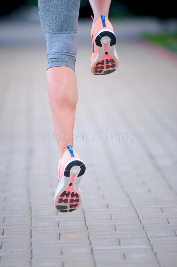 feet of an athlete running on a park pathway training for fitness and healthy lifestyle stock photo