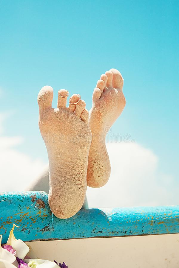 Feet in the sand. Wedding rings royalty free stock photo
