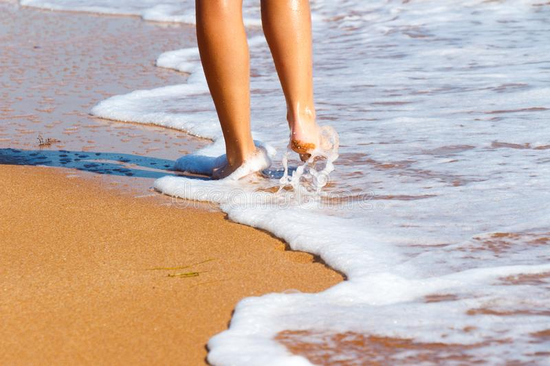 Feet barefoot girl near the water`s edge by the sea stock photo