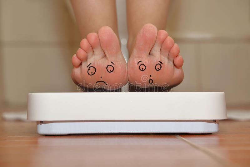 Feet on bathroom scale. With hand drawn sad cute faces stock photo
